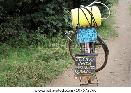 A bicycle carrying an important message (Money Can Not Buy Happiness) in Kenya, Africa. The yellow container is for freshwater. - stock photo