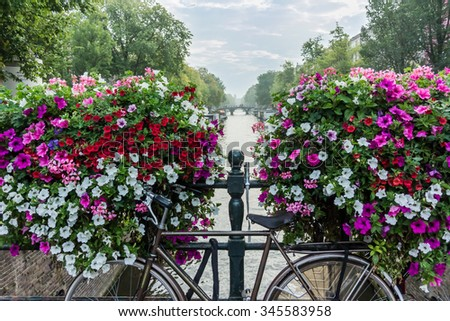 A bicycle in front of flower boxes and a canal in Amsterdam - stock photo