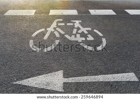 A bicycle lane with arrow on the asphalt - stock photo