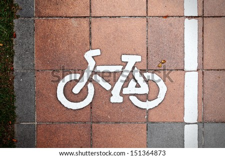A bicycle symbol imprint on a grungy stone pavement.