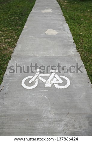 A bicycle symbol on a concrete bicycle lane through a green outdoor recreational park.  - stock photo