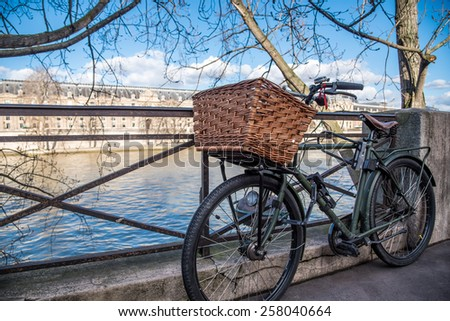 A bicycle with a wicker basket leans against a railing on the banks of the Seine River in Paris France. - stock photo