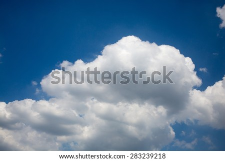 a big and fluffy cumulonimbus cloud in the blue sky  - stock photo