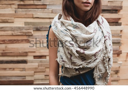 A big beautiful scarf on girl's neck. Small depth of field. Film grain effect.