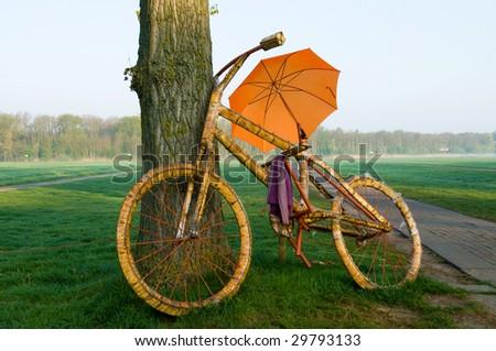 A big bicycle with an orange umbrella - stock photo