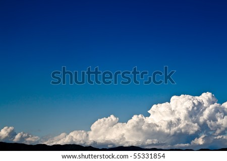 A big cloud over the horizon line, leaving a wide, empty space on the deep blue sky. - stock photo