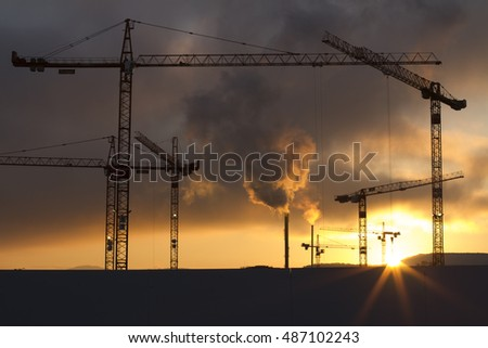 A big construction site at sunrise with several cranes.