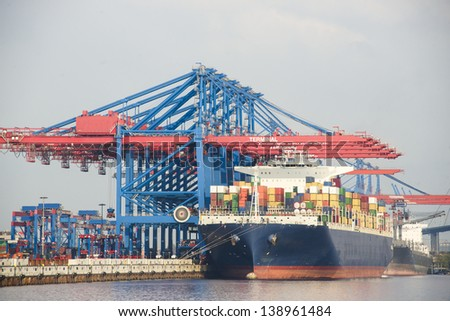 a big container ship in the port terminal is loaded