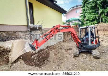 A big family house is being rebuilt with the help of an excavator - stock photo