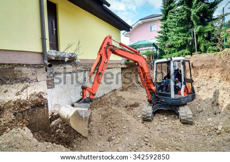 A big family house is being rebuilt with the help of an excavator. Digging the brick and concrete foundation for hydro isolation of basement. - stock photo