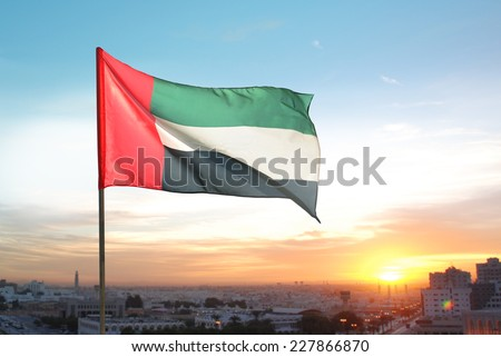 A big flag of UAE flying high on the city of Sharjah, UAE. A National Day celebration on 2nd December. - stock photo