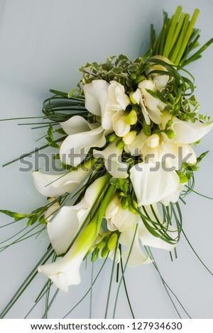 A big flower bouquet filled with calla lillies and other plants. - stock photo