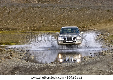 A big four by four off road car crossing a river stream in the Icelandic Tundra - stock photo