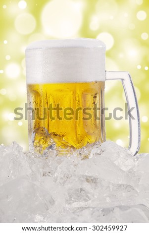 A big glass full of fresh beer with froth and ice cube, shot with bokeh background