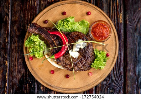a big grilled steak on a wooden plate, top view - stock photo
