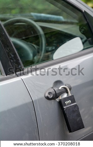 A big lock on a car door handle. Crime concept