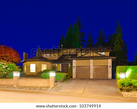 A big luxury house with double  garage doors in suburbs at dusk ( night ) in Vancouver, Canada