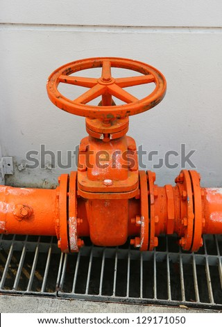 A big orange color water supply main pipeline with a stopcock valve against a concrete wall. - stock photo