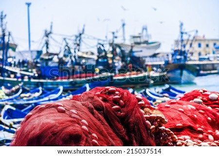A big pile of red fishing nets on the forground of busy harbor with big ships - stock photo
