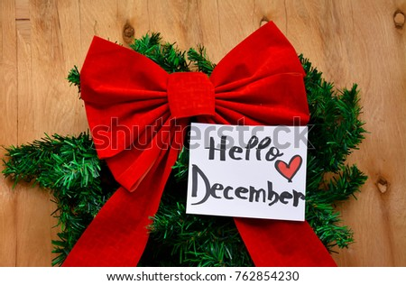 A Big Red Christmas Bow Over A Branch Of Christmas Tree And Hello December  Text On