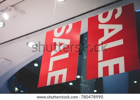 a big red sale advertisement sign at the clothing shop at the department store or mall in the major discount season