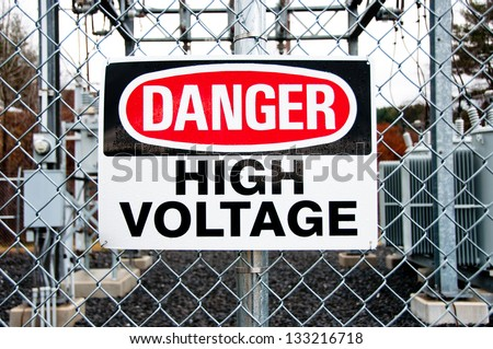 A big red, white and black danger warns trespassers away from this substation. - stock photo