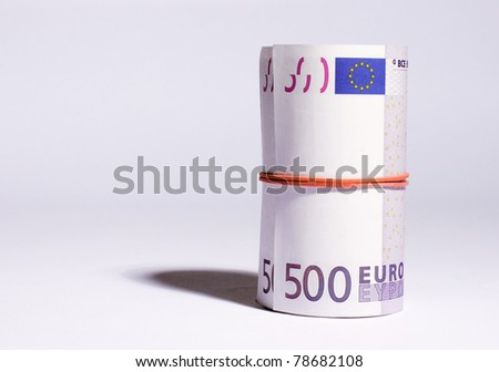 A big roll of euro banknotes, only two 500 notes are visible. - stock photo