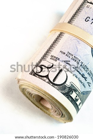 A big rolled wad of cash worth many thousand dollars - stock photo