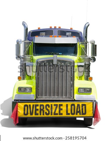 A big semi tractor 18 wheel truck with a big OVERSIZE LOAD banner and red flags on the front of the truck - stock photo