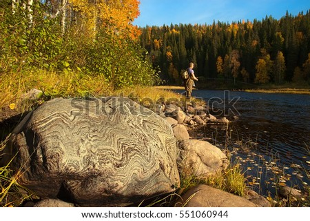 A big stone with beautiful texture. Fisherman on background.