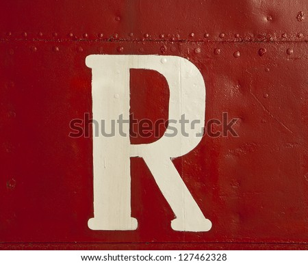 A big white letter 'R', part of a ship's name, surrounded by a sea of intense red paint on the metal hull of the boat. - stock photo