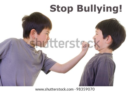 A bigger boy bullying a smaller boy - stock photo