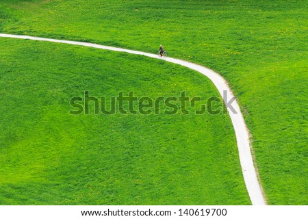 A biker riding next to grassland - stock photo