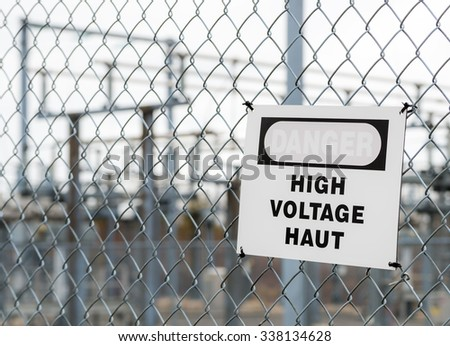 A bilingual faded High Voltage sign on a chain link fence, on a dark cloudy day. The red on the sign is faded and almost invisible. The sign is slightly crooked.  a substation is in the background. - stock photo
