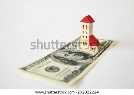 A $100 Bill And A Toy Building