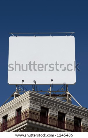 A billboard mounted on the roof of a corner building.