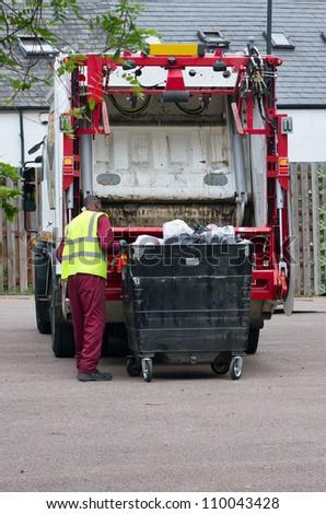 a binman dumping the rubbish - stock photo