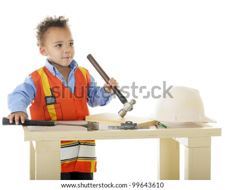 "A biracial preschool ""construction worker"" standing at his workbench holding two hammers.  On a white background. - stock photo"