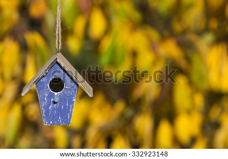 A bird house or bird box in Autumn or Fall sunshine with natural golden leaves background - stock photo