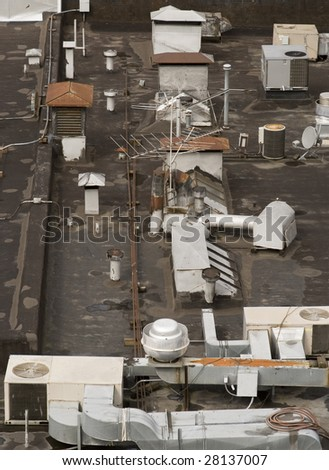 A bird's eye view of a buildings roof with antennas, AC vents, and ventilation. - stock photo