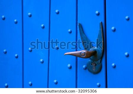A bird shaped door handle on a blue door. - stock photo