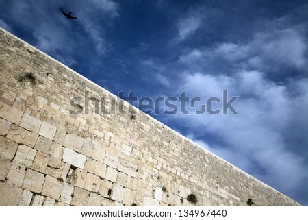 A bird soaring above one of the most sacred places to the Jewish people - the Wailing Wall in the old city of Jerusalem, Israel. - stock photo