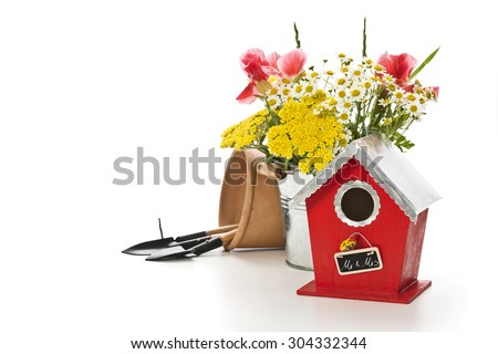 a birdhouse with flowers and gardening tools on white background and a tag: Mr. & Mrs. - stock photo