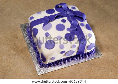 A birthday cake with fondant ribbon and polka-dots. - stock photo