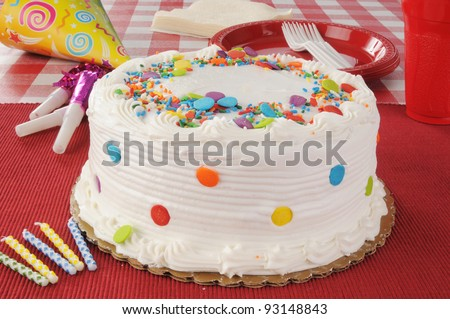 A birthday cake with party streamers, candles and plastic plates - stock photo