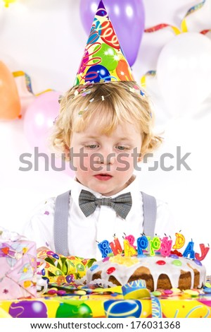 A birthday child with cake and presents blowing out candles.