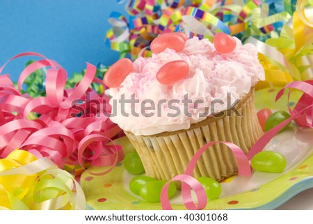 A birthday cupcake with colorful party decorations, horizontal with copy space, selective focus