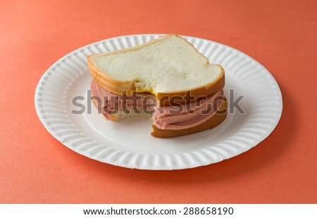 A bitten bologna sandwich with mustard and white bread on a paper plate atop an orange table top. - stock photo