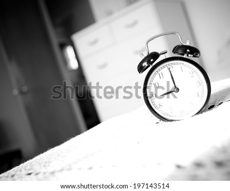 A black alarm clock on a white tablecloth.