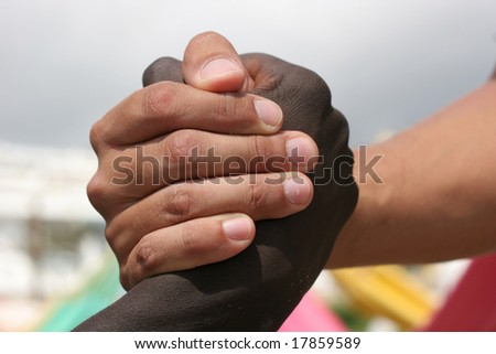 A black and a white person shake hands